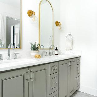 Foto di una stanza da bagno classica con ante con bugna sagomata, ante grigie, pareti bianche, lavabo sottopiano, pavimento grigio, top bianco e due lavabi