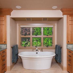 Inredning av ett amerikanskt stort grön grönt en-suite badrum, med ett undermonterad handfat, skåp i shakerstil, skåp i mellenmörkt trä, granitbänkskiva, ett fristående badkar, flerfärgad kakel, keramikplattor, beige väggar och klinkergolv i porslin
