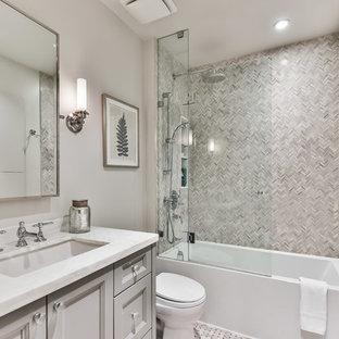 Imagen de cuarto de baño con ducha, tradicional, con armarios con paneles empotrados, puertas de armario grises, bañera empotrada, baldosas y/o azulejos grises, baldosas y/o azulejos en mosaico, paredes grises, suelo con mosaicos de baldosas, lavabo bajoencimera, suelo multicolor y encimeras blancas