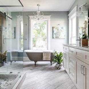 Esempio di una stanza da bagno tradizionale con ante in stile shaker, ante beige, vasca con piedi a zampa di leone, doccia ad angolo, piastrelle grigie, piastrelle di vetro, pareti grigie, lavabo sottopiano, pavimento grigio, porta doccia a battente e top grigio