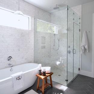 Bild på ett vintage badrum, med ett fristående badkar, en hörndusch, vit kakel, grå väggar och grått golv