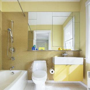 Ispirazione per una stanza da bagno per bambini design di medie dimensioni con ante lisce, ante gialle, vasca ad angolo, vasca/doccia, WC a due pezzi, piastrelle beige, piastrelle gialle, piastrelle di vetro, pareti gialle, pavimento con piastrelle in ceramica e lavabo integrato