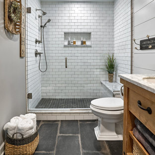 This is an example of a mid-sized country master bathroom in Chicago with furniture-like cabinets, distressed cabinets, white tile, marble benchtops, white benchtops, a single vanity, a freestanding vanity, an alcove shower, a two-piece toilet, ceramic tile, grey walls, porcelain floors, black floor, a hinged shower door, a shower seat, planked wall panelling and an undermount sink.