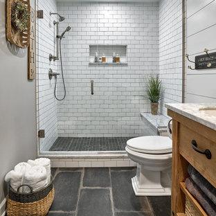 シカゴの中くらいのカントリー風おしゃれなマスターバスルーム (家具調キャビネット、ヴィンテージ仕上げキャビネット、白いタイル、大理石の洗面台、白い洗面カウンター、洗面台1つ、独立型洗面台、アルコーブ型シャワー、分離型トイレ、セラミックタイル、グレーの壁、磁器タイルの床、黒い床、開き戸のシャワー、シャワーベンチ、塗装板張りの壁、アンダーカウンター洗面器) の写真