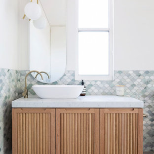 Inspiration for a contemporary bathroom in Other with louvered cabinets, beige cabinets, gray tile, mosaic tile, white walls, a vessel sink, grey floor and white benchtops.
