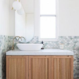 Réalisation d'une salle de bain design avec un placard à porte persienne, des portes de placard beiges, un carrelage gris, carrelage en mosaïque, un mur blanc, une vasque, un sol gris et un plan de toilette blanc.