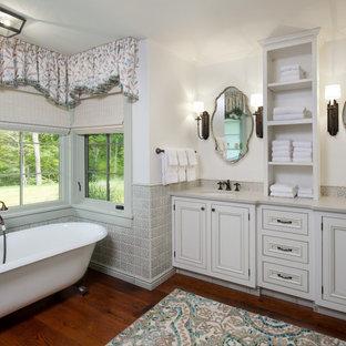 Idéer för att renovera ett stort vintage grå grått en-suite badrum, med grå skåp, ett badkar med tassar, grå kakel, keramikplattor, vita väggar, mellanmörkt trägolv, ett undermonterad handfat, bänkskiva i kvarts och luckor med infälld panel