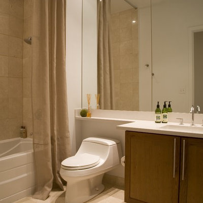 Example of a trendy beige tile tub/shower combo design in DC Metro with an integrated sink, shaker cabinets, medium tone wood cabinets, a one-piece toilet and white countertops