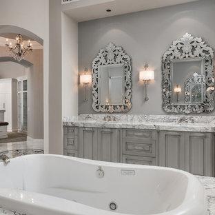Esempio di un'ampia stanza da bagno padronale mediterranea con consolle stile comò, ante grigie, vasca da incasso, doccia aperta, WC monopezzo, piastrelle multicolore, piastrelle a mosaico, pareti beige, pavimento in marmo, lavabo da incasso, top in marmo, pavimento grigio e doccia aperta