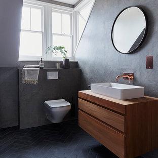 Foto de cuarto de baño con ducha, minimalista, con armarios con paneles lisos, puertas de armario de madera oscura, sanitario de pared, paredes grises, lavabo sobreencimera, encimera de madera, suelo negro y encimeras marrones