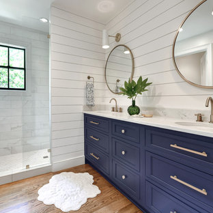 Inspiration for a transitional white tile medium tone wood floor and brown floor bathroom remodel in Charleston with recessed-panel cabinets, blue cabinets, white walls, an undermount sink and white countertops