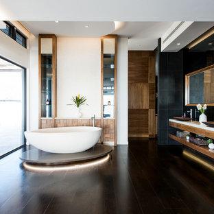 Immagine di una stanza da bagno padronale tropicale con nessun'anta, ante marroni, vasca freestanding, pareti bianche, parquet scuro, lavabo a bacinella e pavimento marrone