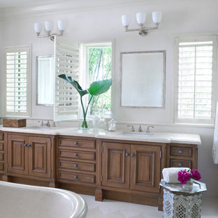 Example of a large tuscan master porcelain floor and white floor freestanding bathtub design in Miami with beaded inset cabinets, light wood cabinets, beige walls, a drop-in sink and granite countertops