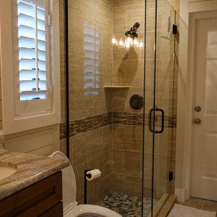他の地域の小さいトランジショナルスタイルのおしゃれなバスルーム (浴槽なし) (シェーカースタイル扉のキャビネット、濃色木目調キャビネット、コーナー設置型シャワー、分離型トイレ、ベージュのタイル、磁器タイル、白い壁、ラミネートの床、アンダーカウンター洗面器、珪岩の洗面台、ベージュの床、開き戸のシャワー、ベージュのカウンター) の写真
