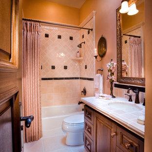 Ispirazione per una stanza da bagno classica di medie dimensioni con ante con bugna sagomata, ante in legno bruno, vasca ad alcova, vasca/doccia, WC a due pezzi, piastrelle rosa, piastrelle in ceramica, pareti rosa, pavimento in pietra calcarea, lavabo sottopiano e top piastrellato