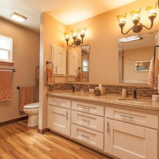 ロサンゼルスの中サイズのトランジショナルスタイルのおしゃれなマスターバスルーム (アンダーカウンター洗面器、シェーカースタイル扉のキャビネット、白いキャビネット、クオーツストーンの洗面台、アルコーブ型浴槽、コーナー設置型シャワー、分離型トイレ、ベージュのタイル、セラミックタイル、ベージュの壁、淡色無垢フローリング) の写真