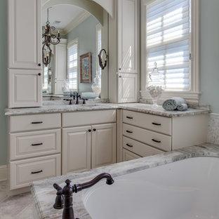 Ispirazione per una stanza da bagno padronale tradizionale con ante con bugna sagomata, ante turchesi, vasca sottopiano, pareti blu, lavabo sottopiano, top in granito, pavimento beige e top multicolore