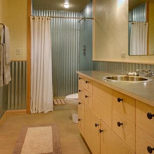 シアトルの中くらいのコンテンポラリースタイルのおしゃれなバスルーム (浴槽なし) (フラットパネル扉のキャビネット、淡色木目調キャビネット、アルコーブ型シャワー、一体型トイレ、グレーのタイル、メタルタイル、ベージュの壁、コンクリートの床、オーバーカウンターシンク、ラミネートカウンター) の写真