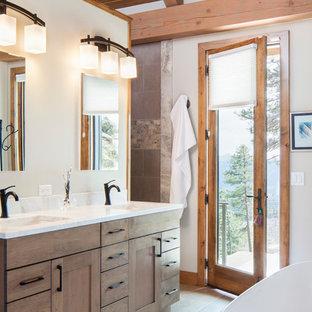 Exemple d'une salle de bain principale montagne avec des portes de placard en bois brun, un mur blanc, un lavabo encastré, un sol gris et un plan de toilette blanc.