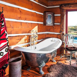 Diseño de cuarto de baño principal, rústico, de tamaño medio, con armarios tipo mueble, puertas de armario con efecto envejecido, ducha a ras de suelo, paredes marrones, suelo de madera en tonos medios, encimera de madera, bañera con patas y lavabo encastrado