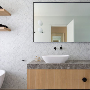 Photo of a mid-sized contemporary master bathroom in Sydney with flat-panel cabinets, brown cabinets, a freestanding tub, a corner shower, gray tile, marble, grey walls, a vessel sink, an open shower and grey benchtops.