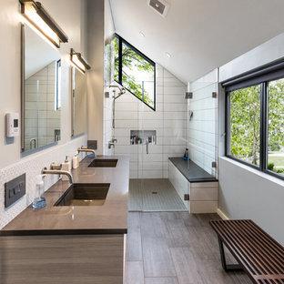 オレンジカウンティの中サイズのコンテンポラリースタイルのおしゃれなバスルーム (浴槽なし) (コーナー設置型シャワー、白いタイル、ベージュの壁、アンダーカウンター洗面器、開き戸のシャワー、フラットパネル扉のキャビネット、淡色木目調キャビネット、磁器タイル、無垢フローリング、珪岩の洗面台、茶色い床、グレーの洗面カウンター) の写真