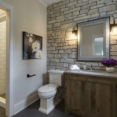 Example of a mid-sized farmhouse 3/4 white tile and ceramic tile porcelain tile and gray floor corner shower design in Minneapolis with medium tone wood cabinets, a two-piece toilet, gray walls, shaker cabinets, an undermount sink, quartz countertops, a hinged shower door and gray countertops