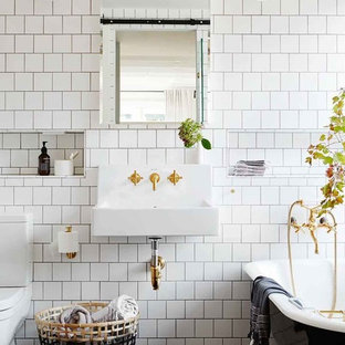 Design ideas for a traditional 3/4 bathroom in Melbourne with a claw-foot tub, a two-piece toilet, white tile, a wall-mount sink and black floor.