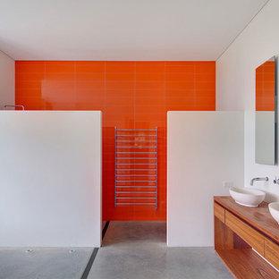 Idéer för att renovera ett funkis brun brunt badrum, med ett fristående handfat, släta luckor, skåp i mellenmörkt trä, träbänkskiva, orange kakel, keramikplattor, vita väggar, betonggolv, en kantlös dusch och grått golv