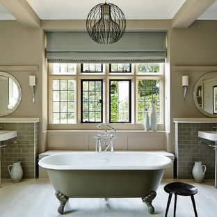 Inspiration for a medium sized classic ensuite bathroom in London with grey tiles, metro tiles, a claw-foot bath, a shower/bath combination, beige walls, light hardwood flooring, a console sink, beige floors and an open shower.