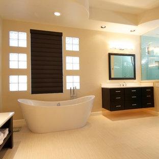 Immagine di una stanza da bagno moderna con ante in stile shaker, ante in legno bruno, lavabo sottopiano, top in granito, vasca freestanding, doccia alcova, piastrelle beige, piastrelle diamantate, pareti beige, pavimento in bambù e porta doccia a battente