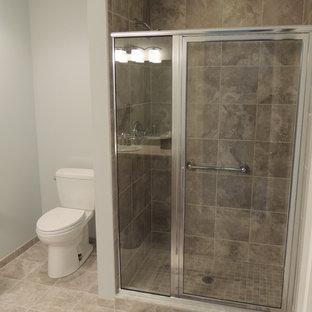 Klassisk inredning av ett mellanstort badrum med dusch, med skåp i shakerstil, skåp i mellenmörkt trä, en dusch i en alkov, en toalettstol med hel cisternkåpa, beige kakel, stenkakel, grå väggar, kalkstensgolv, ett nedsänkt handfat och laminatbänkskiva
