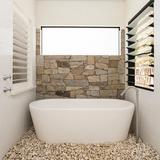 Example of a mid-sized farmhouse master beige tile and stone tile freestanding bathtub design in Dunedin with white walls