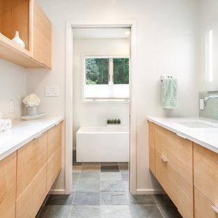 Immagine di una stanza da bagno moderna di medie dimensioni con ante lisce, ante in legno chiaro, vasca freestanding, piastrelle blu, piastrelle di vetro, pareti bianche, pavimento in ardesia, lavabo sottopiano, pavimento grigio e porta doccia scorrevole