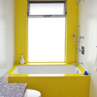 Неиссякаемый источник вдохновения для домашнего уюта: детская ванная комната среднего размера в стиле ретро с белыми фасадами, мраморной столешницей, желтой плиткой, стеклянной плиткой, полом из мозаичной плитки, плоскими фасадами, ванной в нише, душем над ванной, желтыми стенами и раздельным унитазом