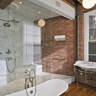 Large industrial master bathroom in New York with white tile, gray tile, a freestanding tub, an alcove shower, marble, red walls, medium hardwood floors, a console sink, marble benchtops, open cabinets, medium wood cabinets, brown floor and an open shower.