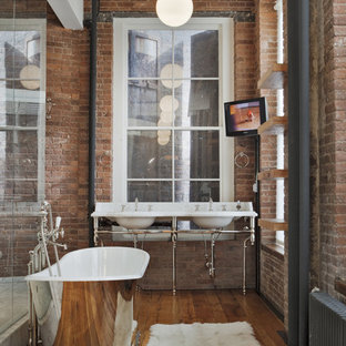 Imagen de cuarto de baño principal, industrial, grande, con bañera exenta, ducha empotrada, paredes rojas, suelo de madera en tonos medios, lavabo tipo consola, encimera de mármol, armarios abiertos, puertas de armario de madera oscura, baldosas y/o azulejos rojos y ducha abierta
