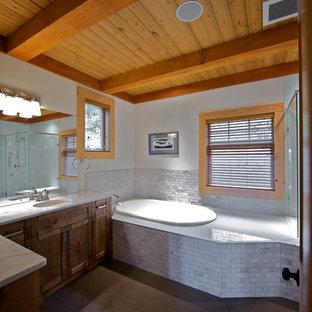 バンクーバーのコンテンポラリースタイルのおしゃれな浴室 (アンダーカウンター洗面器、シェーカースタイル扉のキャビネット、グレーのタイル、中間色木目調キャビネット、白い壁、コンクリートの床、ドロップイン型浴槽) の写真