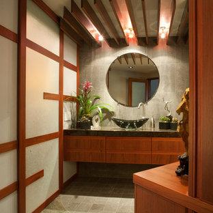Immagine di una stanza da bagno con doccia etnica di medie dimensioni con ante lisce, ante in legno scuro, piastrelle grigie, piastrelle in ceramica, pareti grigie, pavimento con piastrelle in ceramica, lavabo a bacinella, top in superficie solida e pavimento grigio