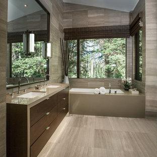 Стильный дизайн: главная ванная комната среднего размера в современном стиле с врезной раковиной, плоскими фасадами, темными деревянными фасадами, полновстраиваемой ванной, серой плиткой, столешницей из кварцита, каменной плиткой, серыми стенами и полом из известняка - последний тренд