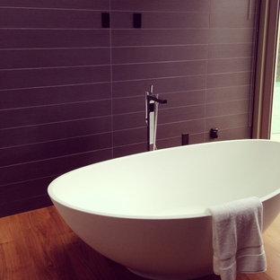 Diseño de cuarto de baño principal, contemporáneo, de tamaño medio, con bañera exenta, baldosas y/o azulejos negros, suelo de madera en tonos medios y paredes púrpuras