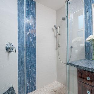 Пример оригинального дизайна: маленькая главная ванная комната в морском стиле с врезной раковиной, фасадами с выступающей филенкой, темными деревянными фасадами, столешницей из искусственного кварца, угловым душем, синей плиткой, стеклянной плиткой, серыми стенами и полом из керамогранита
