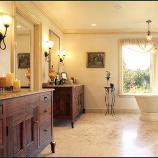 Large elegant master brown tile and porcelain tile yellow floor bathroom photo in Portland with an undermount sink, furniture-like cabinets, dark wood cabinets, granite countertops, a two-piece toilet, yellow walls and a hinged shower door