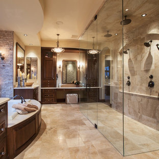 Design ideas for a large mediterranean ensuite bathroom in Calgary with recessed-panel cabinets, dark wood cabinets, a built-in bath, a double shower, beige tiles, stone tiles, beige walls, marble flooring, a submerged sink, engineered stone worktops, beige floors and a hinged door.