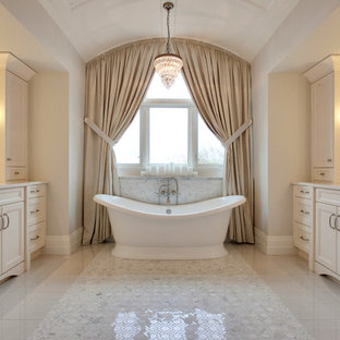 Freestanding bathtub - large french country master beige tile and ceramic tile ceramic floor freestanding bathtub idea in Calgary with an undermount sink, raised-panel cabinets, beige cabinets, granite countertops and beige walls