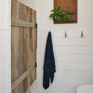 Inredning av ett lantligt stort badrum med dusch, med en dusch i en alkov, vit kakel, keramikplattor, vita väggar, klinkergolv i keramik, blått golv och dusch med gångjärnsdörr