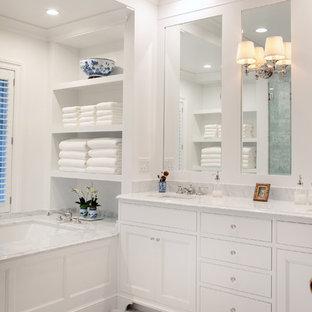 Diseño de cuarto de baño principal, tradicional, de tamaño medio, con armarios con paneles empotrados, puertas de armario blancas, bañera encastrada sin remate, paredes blancas, lavabo bajoencimera, suelo blanco, encimeras blancas, ducha empotrada, baldosas y/o azulejos de mármol, suelo de mármol, encimera de mármol y ducha con puerta con bisagras