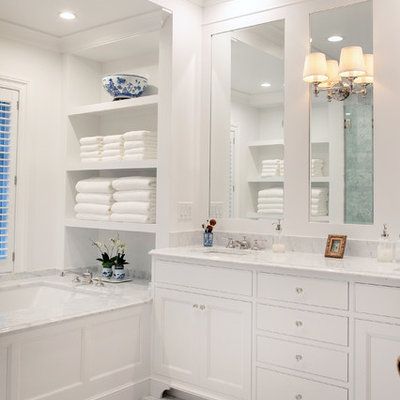 Mid-sized elegant master marble tile white floor and marble floor alcove shower photo in Milwaukee with recessed-panel cabinets, white cabinets, an undermount tub, white walls, an undermount sink, white countertops, marble countertops and a hinged shower door