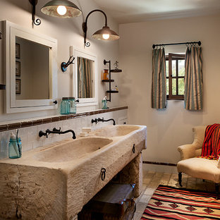 Example of a mid-sized mountain style brick floor bathroom design in Phoenix with beige walls, wood countertops and an integrated sink