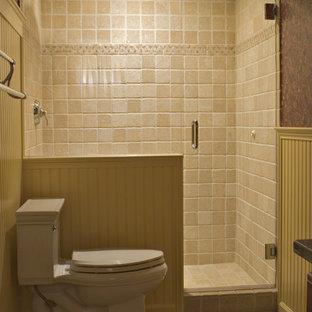 Diseño de cuarto de baño de estilo de casa de campo, de tamaño medio, con lavabo bajoencimera, puertas de armario de madera oscura, encimera de granito, ducha empotrada, sanitario de dos piezas, baldosas y/o azulejos beige, baldosas y/o azulejos de piedra, paredes amarillas y suelo de baldosas de porcelana